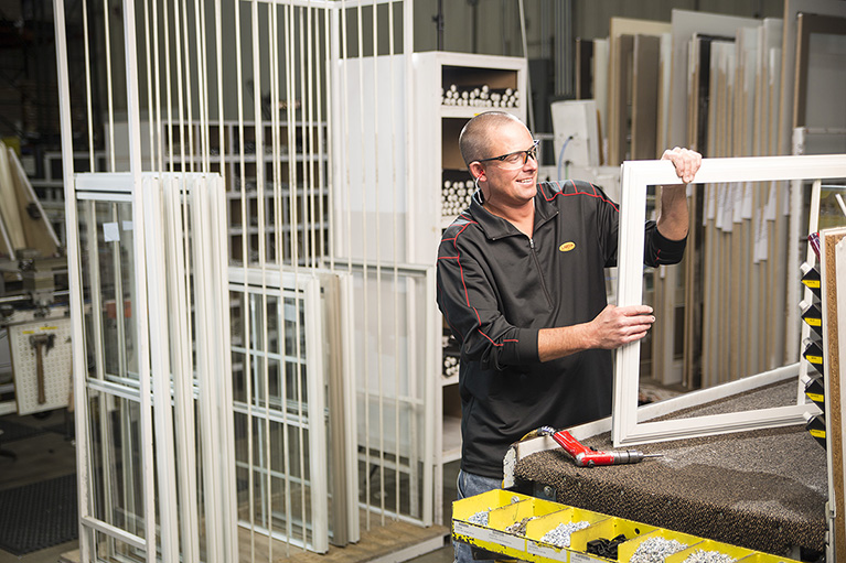 Larson Manufacturing Employee works on storm windows